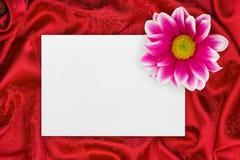 Salutation de la carte de papier et de la fleur sur le tissu rouge Photos stock