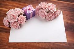 Salutation de la carte vierge avec les roses et le cadeau Photographie stock