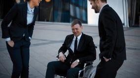 Salutation et plaisanterie d'hommes d'affaires avec l'homme d'estropié de handicapés banque de vidéos