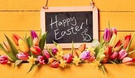 Salutation heureuse de vacances de Pâques avec des fleurs de ressort photo stock