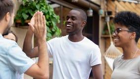 Salutation masculine diverse heureuse d'amis donnant la haute cinq à se réunir photo stock