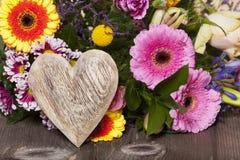 Salutations de fleur avec un coeur en bois Photos stock