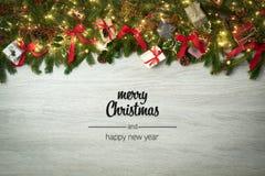 Salutations de Joyeux Noël et de bonne année en bois blanc vertical de vue supérieure avec des branches, des rubans et des lumièr image stock