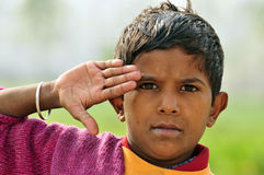 Salute. Poor indian boy in saluting pose Stock Photo