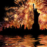 Salute. Silhouette statue of liberty on firework background with reflection from water Stock Photos