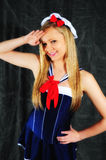 Salute. Young female fashion model wearing a lovely sailor outfit saluting to the camera standing against a charcoal back ground Royalty Free Stock Photo