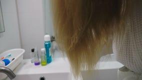 Salute dei capelli, concetto di perdita di capelli Donna che pettina i suoi capelli asciutti nocivi biondi nel bagno video d archivio