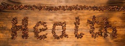 Salute dell'iscrizione dai pinoli su un fondo del bordo di legno immagine stock libera da diritti