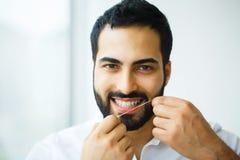 Salute dentale Uomo con il bello sorriso che Flossing i denti sani immagine stock