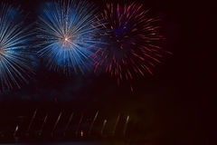 Salute, fireworks at the sea shore, reflected in the water. A beautiful night view of lights in the form of feathers.n Stock Photo