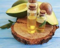 Salute organica dell'olio di bellezza della bottiglia dell'avocado fresco un fondo di legno blu, antiossidante organico fotografie stock libere da diritti