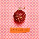 Saluti di stagioni della palla e del testo di Natale su un backgrou variopinto Fotografia Stock