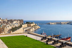 Saluting Battery and Fort Ricasoli in Valletta. Valletta, Malta - November 8, 2015: View of Valletta from the Upper Barrakka Gardens, with the Grand Harbour Royalty Free Stock Photo
