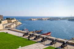 Saluting Battery and Fort Ricasoli in Valletta. Valletta, Malta - November 8, 2015: View of Valletta from the Upper Barrakka Gardens, with the Grand Harbour Royalty Free Stock Photos
