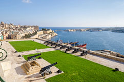 Saluting Battery and Fort Ricasoli in Valletta. Valletta, Malta - November 8, 2015: View of Valletta from the Upper Barrakka Gardens, with the Grand Harbour Stock Photos