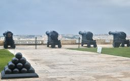 Four heavy Guns and saluting battery in the upper barrakka gardens. In the foreground a pyramid of cannonballs royalty free stock image
