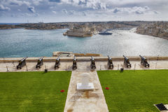 The Saluting Battery. Skyline of the Maltese capital city Valletta. The Saluting Battery of La Valletta and Fort St. Angelo of La Vittoriosa in Malta Royalty Free Stock Photos