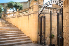 Saluting battery, Valleta, Malta, entrance. Entrance in stairway with saluting battery sign above the barred opened door Stock Images