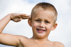 Saluting boy. The little smiling boy saluting as soldiers Royalty Free Stock Images