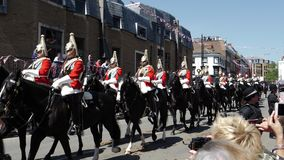Saluting the Royal Guards march in street around Windsor Castle. WINDSOR, UNITED KINGDOM - MAY 19, 2018: View of team of Royal Guards march in street around stock video footage