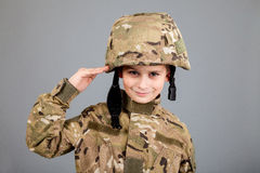 Saluting soldier. Young boy dressed like a soldier Royalty Free Stock Image