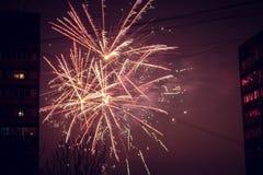 Saluto di notte Linee di esplosione di colori differenti Scoppi fra le case fotografia stock