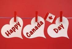Saluto felice del messaggio di giorno del Canada con la bandiera canadese della foglia di acero che pende dai pioli su una linea Immagini Stock