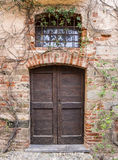 Saluzzo old door. Facade of red brick retro style house with black wooden gate at entrance in Italy Royalty Free Stock Photo