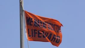 Salva-vidas alaranjada Flag em uma praia em Grécia que funde no vento em um dia de verão