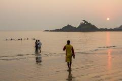 A salva-vidas na roupa vermelha amarela está olhando a natação dos povos no mar na noite a fotografia de stock