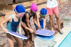 Salva-vidas que ajuda a crianças para arranjar kickboards na piscina fotos de stock