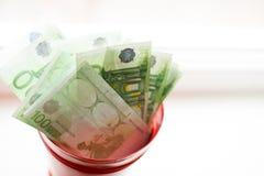 Salvadanaio, euro fattura in secchio sulla finestra bianca Fondo leggero Posto per testo Vista superiore immagine stock libera da diritti
