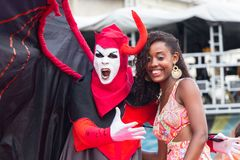 Carnival celebration at Pelourinho in Salvador Bahia, Brazil. Salvador Bahia, Brazil - February 12th, 2018: A girl is takiing a photo with a reveler with Devil Royalty Free Stock Photography
