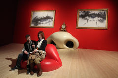 Salvador Dali exhibition in the Pompidou Centre, Paris. PARIS, FRANCE - JANUARY 7, 2013: Visitors take a picture as they sit at the Mae West Lips Sofa inside Stock Image
