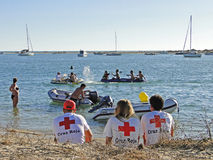 Salvage and rescue costs. Three volunteers from the Red Cross observed a group of turis having fun in the sea Stock Photography