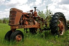 Salvaged tractor in the bushes Royalty Free Stock Images