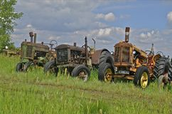 Salvaged tractors line up in junkyard Royalty Free Stock Photos