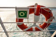 Salvagente con il segno su un recinto del traghetto, con il sole ed il mare in backgro Fotografie Stock Libere da Diritti