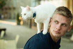 Salvaje y nacional al mismo tiempo Michael Showalter Gato pedigrí lindo del control muscular del hombre El gato se coloca en la p foto de archivo
