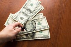 Salvamento, imposto ou procurando da finança pelo conceito do rendimento, vidro da lente de aumento na pilha de cédulas do dólar  fotos de stock