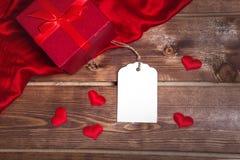 Salvar a caixa de presente vermelha envolvida estreia da transferência e o vale-oferta na tabela de madeira pode usar-se no dia d Fotos de Stock