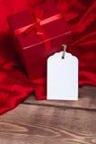 Salvar a caixa de presente vermelha envolvida estreia da transferência e o vale-oferta na tabela de madeira pode usar-se no dia d Foto de Stock