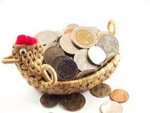 Salvar o dinheiro com coleção de moedas na cesta de weave Imagem de Stock Royalty Free
