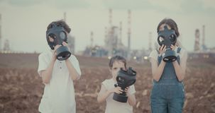 Salvar a planta Crianças que vestem máscaras de gás perto de uma grande refinaria de petróleo vídeos de arquivo