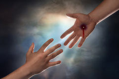 Salvation. Hand of Christ reaching down from heaven to grab the hand of man Royalty Free Stock Photo