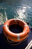 Salvation. A bright orange lifebuoy on a boat royalty free stock photos