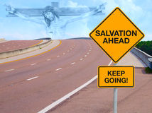 SALVATION AHEAD Road Sign w Jesus in Sky on Horizon. Road sign that says SALVATION AHEAD KEEP GOING with a winding road leading up to a sky with Jesus in the Stock Photo
