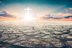 Salvation concept: Concept conceptual White cross religion symbol silhouette in grass over sunset or sunrise sky royalty free stock image