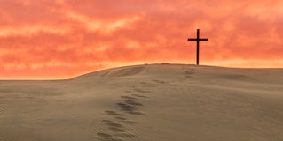 Salvation Foot Steps. Black cross on a sand dune with foot steps leading up to it Royalty Free Stock Image