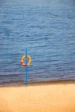 Salvavidas anaranjado que cuelga cerca del agua Imagenes de archivo